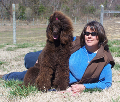 Woman Laying Outside With a Chocolate Standard Poodle