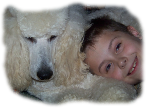 Child Smiling With a Standard Poodle